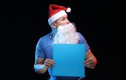 Porträtschauspielermann in der Kappe und im Bart von Santa Claus mit einem Blatt Papier für Anmerkungen in den Händen Lizenzfreie Stockbilder