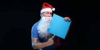 Porträtschauspielermann in der Kappe und im Bart von Santa Claus mit einem Blatt Papier für Anmerkungen in den Händen Stockfotografie