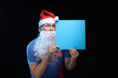Porträtschauspielermann in der Kappe und im Bart von Santa Claus mit einem Blatt Papier für Anmerkungen in den Händen Lizenzfreies Stockfoto