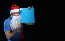 Porträtschauspielermann in der Kappe und im Bart von Santa Claus mit einem Blatt Papier für Anmerkungen in den Händen Stockbild