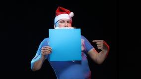 Porträtschauspielermann in der Kappe und im Bart von Santa Claus mit einem Blatt Papier für Anmerkungen in den Händen Lizenzfreie Stockfotos