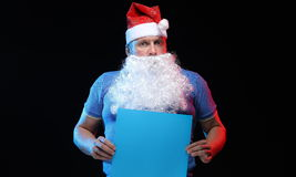 Porträtschauspielermann in der Kappe und im Bart von Santa Claus mit einem Blatt Papier für Anmerkungen in den Händen Lizenzfreies Stockbild