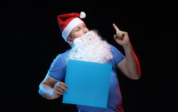 Porträtschauspielermann in der Kappe und im Bart von Santa Claus mit einem Blatt Papier für Anmerkungen in den Händen Stockfotos