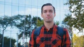 Porträtt av en stilig ung man i plaiskjortan och med en ryggsäck som tittar på kameran Stadsbyggnad av stort glas lager videofilmer