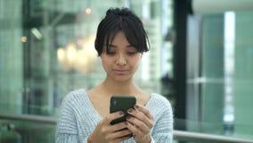 Porträtwannen-Schusszeitlupe der ernsten asiatischen weiblichen Stellung, die am Telefon schreibt stock video