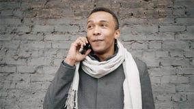Porträtzeitlupe geschossen vom afroen-amerikanisch Mann, der am Telefon spricht Hübscher Afroamerikanerkerl in einem Mantel und i stock video footage