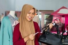 Portr?t asiatisches hijab der weiblichen Inhaber- und Kost?mstellung mit schwarzem Geldbeutel in ihrem Boutiquenmodespeicher, jun lizenzfreies stockbild
