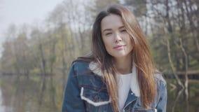 Portr?t der attraktiven jungen Frau, die auf dem Riverbank, schauend in der Kamera sitzt Verbindung mit Natur Sch?n stock video