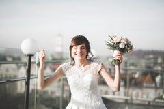 Portr?t der erstaunlichen Braut mit dem langen Haar, das mit gro?em Blumenstrau? aufwirft stockbild
