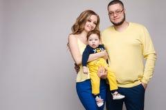 Portr?t der gl?cklichen Familie von drei Leuten, die an der Kamera aufwerfen lizenzfreies stockfoto