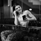 Portr?t der jungen Sportlerin mit Smartphone h?rend Musik in der Turnhalle lizenzfreie stockfotos