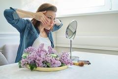 Portr?t der reifen Frau mit Make-up-Spiegel ihr Gesicht und Hals, sch?ne Frau massierend 40 Jahre alt stockfoto