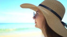 Portr?t der sch?nen jungen Frau mit Hut und Sonnenbrille auf Strand stock footage