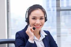 Portr?t des gl?cklichen l?chelnden weiblichen Kundenbetreuungs-Telefonbetreibers am Arbeitsplatz Asiatisch lizenzfreies stockbild
