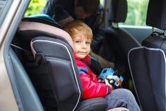 Portr?t des h?bschen Kleinkindjungen, der im Autositz sitzt Kindertransportsicherheit Vaterclip auf einem anderen Sohn an stockfoto