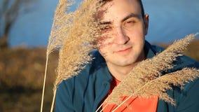 Portr?t des h?bschen l?chelnden Mannes mit trockenem Gras, deckt im Freien mit Schilf stock video