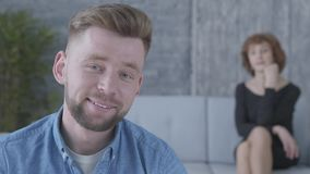 Portr?t des jungen Mannes im blauen Hemd, das im Vordergrund sitzt Die unscharfe Zahl reifer Dame auf dem Sofa auf stock video footage