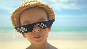 Portr?t des netten kleinen Jungen im Strohhut mit der Sonnenbrille, die auf Sommerstrand steht stock footage