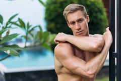 Portr?t des sexy athletischen Mannes in den wei?en Hosen mit dem nackten Torso, der im tropischen Garten stillsteht stockbild