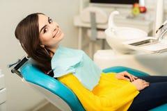 Portr?t einer Frau mit dem toothy L?cheln, das am zahnmedizinischen Stuhl im zahnmedizinischen B?ro sitzt stockbild