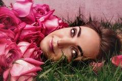 Portr?t einer jungen Frau in den Rosen auf dem Gras Sch?ne Woman lizenzfreie stockfotos
