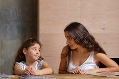 Portr?t einer Mutter, die ihrer kleinen s??en und netten Tochter hilft, ihre Hausarbeit zuhause zu machen Gl?ckliche Familie stockbild