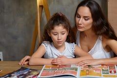 Portr?t einer Mutter, die ihrer kleinen s??en und netten Tochter hilft, ihre Hausarbeit zuhause zu machen Gl?ckliche Familie stockfotos