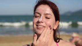 Portr?t einer sch?nen jungen Frau, l?chelnd, in einem Bikini, geschmiertes Gesicht mit Sonnenschutzcreme, Seehintergrund stock footage