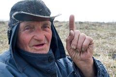 Portr?t eines alten Mannes in unordentliche Kleidung und Hut, die seinen Zeigefinger anhoben, habe ich eine Idee stockfotografie