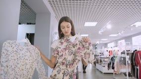 Portr?t eines brunette M?dchens in einem Bekleidungsgesch?ft in einem Mall w?hlt zwischen zwei Kleidern vor einem Spiegel Aufstel stock video footage