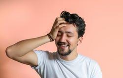 Portr?t eines jungen Mannes mit dem Klammerl?cheln Ein glücklicher junger Mann mit Klammern auf einem rosa Hintergrund lizenzfreie stockbilder