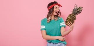 Portr?t eines M?dchens mit einer Ananas auf einem rosa Hintergrund stockfotos
