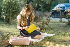 Portr?t im Freien des Schulm?dchens sitzend auf dem Grasleseschulnotizbuch Beginnen Sie die Schule lizenzfreies stockbild