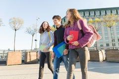 Portr?t im Freien von den Jugendstudenten mit Rucks?cken gehend und sprechend stockbild