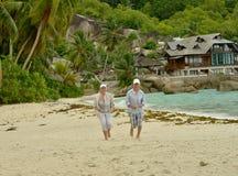 Portr?t von den gl?cklichen ?lteren Paaren, die auf tropischem Strand laufen stockfoto