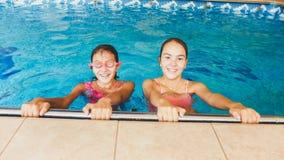 Portr?t von zwei gl?cklichen Freundinnen, die in zuhause Swimmingpool aufwerfen lizenzfreie stockfotos