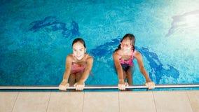 Portr?t von zwei l?chelnden Jugendlichen, die im Pool an der Turnhalle schwimmen stockfotografie