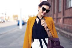 Portr?tmodefrau in der Sonnenbrille gehend auf Stra?e Sie tr?gt die gelbe Jacke und l?chelt, um mit Seiten zu versehen stockfoto