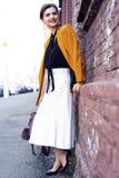 Portr?tmodefrau, die auf Stra?e geht Sie tr?gt die gelbe Jacke und l?chelt, um mit Seiten zu versehen stockbilder