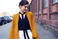 Portr?tmodefrau, die auf Stra?e geht Sie tr?gt die gelbe Jacke und l?chelt, um mit Seiten zu versehen lizenzfreie stockbilder