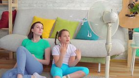Portr?tmutter und -tochter nahe bei dem Fan leidet unter hei?em Wetter stock footage