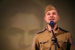 Portra苏联士兵,诗人,播放在黑背景的二战制服的英雄手风琴 库存照片