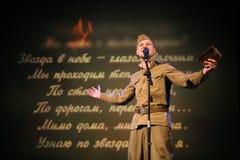 Portra苏联士兵,诗人,播放在黑背景的二战制服的英雄手风琴 免版税图库摄影