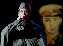 Portra苏联士兵,诗人,播放在黑背景的二战制服的英雄手风琴 免版税库存照片