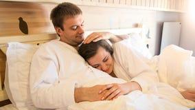 Portrai της όμορφης νέας γυναίκας στο μπουρνούζι που αγκαλιάζει το σύζυγό της στο κρεβάτι στοκ εικόνες