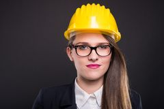 Portrai of attractive young female architect. Or constructor posing on dark background Royalty Free Stock Images