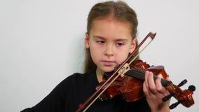 Portrai d'adolescent jouant le violon au-dessus du fond blanc banque de vidéos