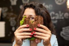 Portrai da mulher moreno caucasiano nova que olha através do sanduíche mordido imagens de stock