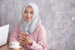 Beautiful muslim women smiling while holding mobilephone. Portrai to of beautiful muslim woman smiling while holding mobilephone with copy space Royalty Free Stock Photography