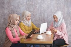 Three siblings wearing hijab are busy on their own gadget. Portrai to fthree siblings wearing hijab are busy on their own gadget Stock Photo